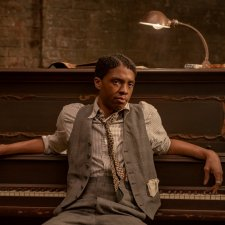 Actor Chadwick Boseman, a Black man wearing a striped shirt, patterned tie, grey vest and pants, sits at a piano, his back to the keyboard
