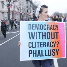 "A woman is particpating in a demonstration on a city street; she carries a sign that reads ""Democracy without cliteracy? Phallusy."""
