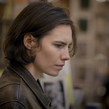 Side profile of Amanda Knox, a white woman with short brown hair. She is wearing a leather jacket. Image from from Ron Blackhurst and Brian McGinn's 2016 film 'Amanda Knox.' Courtesy of Netflix.