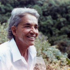 Chavela Vargas is a queer Latin American singer with grey hair. She is wearing a white shirt and is smiling. She is surrounded by trees and shrubs. Image from Catherine Gund and Daresha Kyi's 'Chavela.' Courtesy of Alicia Elena Pérez Duarte, Aubin Pictures.