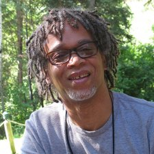 Lewis Erskine (1957-2021) is a middle-aged Black man with short dreads. He is wearing a grey t-shirt and black rimmed glasses. Image courtesy of Jean Tsien