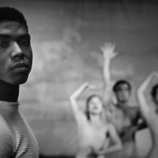 """Black-and-white image of a young Alvin Ailey. He is a Black man with short hair wearing white t-shirt. Behind him are three dancers. Image from Jamila Wignot's """"Ailey"""". Courtesy of NEON."""