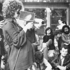 """Black-and-white image of French feminist filmmaker Carole Roussoupolos, whose films are now streaming on """"Another Screen."""" In the photo, she is pregnant and is filming using a handheld camera, with people looking on. Courtesy of Another Screen; Centre Audiovisuel Simone de Beauvoir, Paris."""