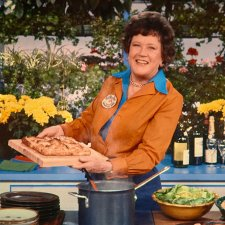 Julia Child is a white chef with short brown wavy hair. Here she is standing in her kitchen holding a tray of pastry. She is wearing a blue shirt underneath another brown one, and is smiling. Image from Julie Cohen and Betsy West's 'Julia.' Courtesy of TIFF.