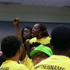 """Caption: Janaé Bonsu is a young Black woman leading an activist gathering. She and her comrades are in yellow shirts that say """"Say Her Name"""". Image for Ashley O'Shay's """"Unapologetic"""". Courtesy of David Magdael & Associates."""