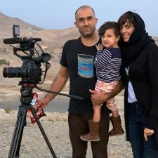 Elizabeth Mirzaei and Gulistan Mirzaei standing in an Afghanistan desert with a camera, in 2019. Gulistan is carrying their daughter, Maryam. Elizabeth is wearing a headscarf, Gulistan is wearing a black t shirt and glasses, Maryam is wearing a striped shirt and floral pants. Image courtesy of the authors.