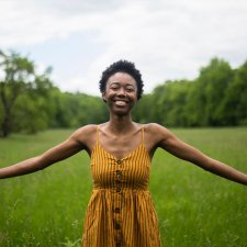 Elodie Edjang, a Black woman with short hair and a yellow dress stands in a grass field.
