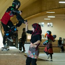 A young Afghani girl in a checkered headscarf helps her friend on a skateboarding ramp. Her friend is wearing skateboarding gear. They're inside a training room with other young skateboarders. Image from Carol Dysinger's 'Learning to Skateboard in a Warzone (If You're a Girl).' Courtesy of the filmmaking team.