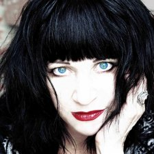 Lydia Lunch, a white woman with black hair cut in bangs. She is wearing bright blue contact lenses and red lipstick. From Beth B's 'Lydia Lunch: The War is Never Over'. Courtesy of Kino Lorber.