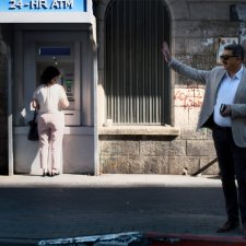 Musa Hadid, the mayor of Ramallah is a middle-aged man with a moustache. He is waving to someone and is wearing sunglasses, and is wearing a grey jacket with a shirt and trousers. There are passersby and an ATM machine behind him. Image from David Osit's 'Mayor.' Courtesy of David Osit and POV.