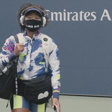 """Tennis player Naomi Osaka, an Afro-Japanese female tennis player on a tennis court wearing a multi-colored jacket, and a mask that says """"Tamir Rice."""" Still from Garrett Bradley's Netflix series, 'Naomi Osaka'. Courtesy of Netflix"""