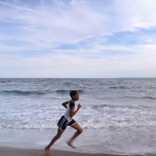 A young Black girl in shorts and a t-shirt runs along the seashore. Tai Sheppard in 'Sisters on Track' (directors: Corinne van der Borch, Tone Grøttjord-Glenne). Courtesy of Netflix