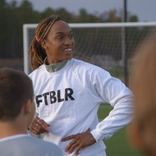 """Soccer player Jessica McDonald is a Black woman in her 30s. Here, she is wearing a white shirt that says """"FTBLR"""" and her hair is tied back. Image from Andrea Nix Fine and Sean Fine's 'LFG.' Courtesy of HBO Max"""