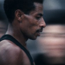Abebe Bikila is a Black Ethiopian marathoner seen here at the 1964 Summer Olympics at Tokyo. He has black hair, a moustache, and is wearing a black vest. Image from Kon Ichikawa's 'Tokyo Olympiad.' Courtesy of The Criterion Collection.