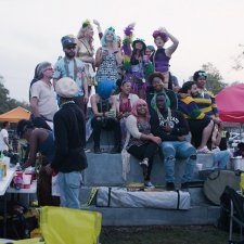 Black and white costumed New Orleanians celebrate Mardi Gras on the pedestal of a now absent confederate monument. From CJ Hunt and Darcy McKinnon's The Neutral Ground. Photo by Paavo Hanninen. Courtesy of POV.