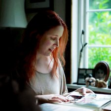 Dylan is a white woman, with red hair, in her early 30s; she is sitting at a desk next to a window, and she is looking at a photo album.