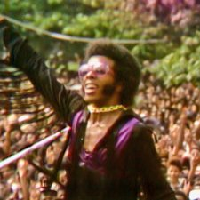 Sly Stone, a Black male musician in violet and black, plays to a huge crowd in Questlove's 'Summer of Soul' (Director: Questlove; Producer: David Dinerstein, Robert Fyvolent, Joseph Patel) Courtesy of Cinetic Media.