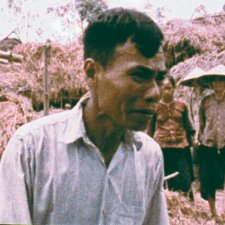 A middle-aged Vietnamese man looks in despair in front of damaged home