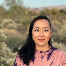 Asian-American adult is standing in front of desert landscape, wearing pink tie-dye tee, black hair passed the shoulders with left side shaved.