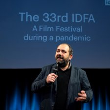 The IDFA festival director, mic in hand and wearing a black jacket, addresses the audience in front of a blue curtain.