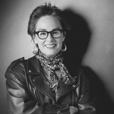 In this black-and-white portrait of Judy Irola, she has short brunette hair and glasses, she is wearing a leather jacket and she is posing with her arms crossed across her chest.