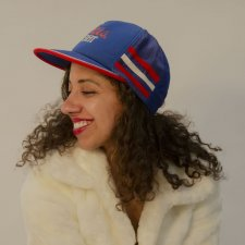 A photo of filmmaker Justine Armen, a mixed-race woman with dark brown curly hair wearing a blue and red baseball cap and white coat, looking to the side and smiling.