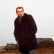 A man in his 30s, wearing a black overcoat, stands on a country road