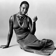 Nina Simone is sitting on the floor with her right arm propping her up. She is wearing a maxi knit dress, large decorative necklace.
