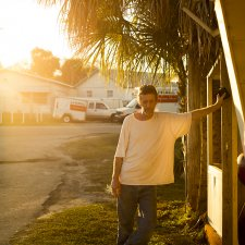 A white man is standing at the entrance of a trailer park