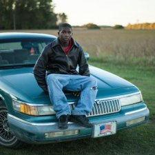 A young Black adult sitting on top of a blue car