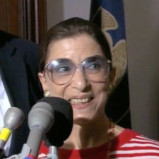 Justice Ginsburg is pictured here at a press conference, in front of a bank of microphones, and she is wearing a red-and-white striped shirt.
