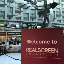 "A red sign with ""Welcome to REALSCREEN SUMMIT 2018"" in front of an open-air business lobby with abstract metal sculpture."