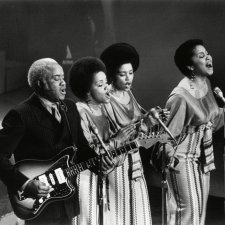 Three Black women in long skirts singing, one Black man playing the guitar. They are on stage. There are three microphones.