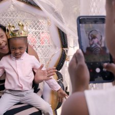 A Black boy, wearing a golden crown and a pink shirt, sits on the lap of a Black woman in a striped dress. A Black girl takes a photo.