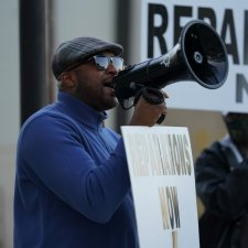 A Black man, wearing a blue polar fleece, leads a protest calling for reparations for victims of the 1921 Tulsa Massacre.