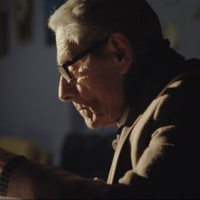 The noir lighting of Sergio dictating a late-night memo; from Maite Alberdi's 'The Mole Agent'