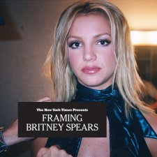 Britney Spears is looking at the camera in a dressing room, wearing a sparkling blue halter top