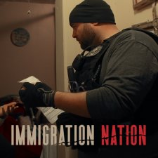 An U.S. Immigration and Customs Enforcement officer is questioning an adult woman inside her home about her documents.