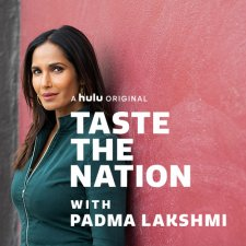 Padma Lakshmi is an Indian woman with straight dark brown hair, wearing a pine green denim jacket, standing against a pink wall