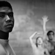 Black and white image of a black man with short dark hair looking into the camera. In the background three dancers strike a pose.