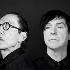 A black and white portrait of two white men both with dark hair. The man on the left has round black glasses and a pencil mustache.