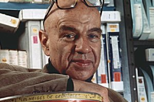 A middle-aged Bud Greenspan posing in front of film tapes. He is bald and is wearing black framed glasses on his head.