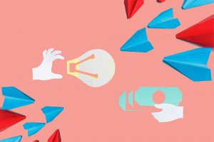 paper cutout of a hand holding a light bulb from the left, a hand holding money from the right; they are flanked by simple plane origamis at the diagonal corners.