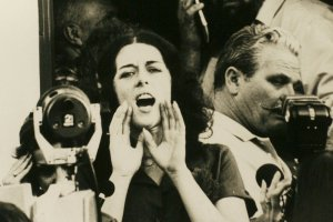 Activist Lois Gibbs is a white woman with short dark hair seen shouting to a crowd in an archival image. From Mark Kitchell's 2012 film 'A Fierce Green Fire'. Courtesy of Mark Kitchell