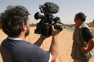 Ross Kauffman (left) is shooting in the field. Subject is n the right, turning away and listening to a walkie talkie.