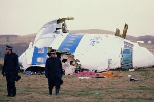 Two police officers in front of a plane wreckage in the field
