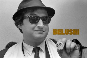 John Belushi is wearing a fedora and black sunglasses, holding up a pin with print of himself
