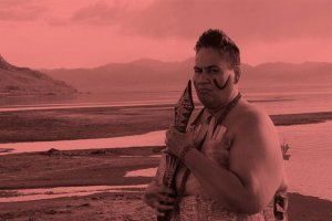 A middle-aged woman with very short hair dressed in traditional Samoan warrior clothes and holding a club near her face and standing at the edge of a lake with mountains in the distance.