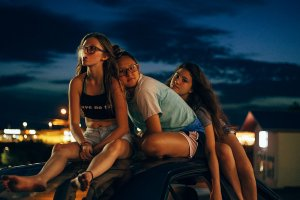 Three teenage girls sit on top of a car. One is smoking.
