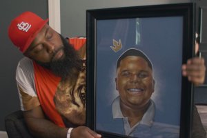 A Black man with a long black beard wearing a red baseball cap and shirt holds a framed painting of a Black boy with a crown on his head.